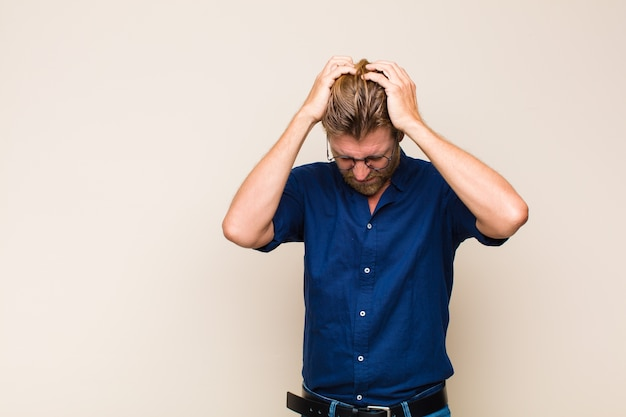 Homem adulto loiro se sentindo estressado e frustrado, levando as mãos à cabeça, sentindo-se cansado, infeliz e com enxaqueca
