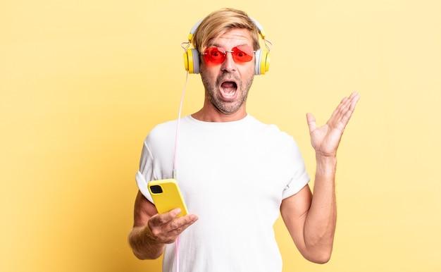 Homem adulto loiro se sentindo feliz e surpreso ao perceber uma solução ou ideia com fones de ouvido