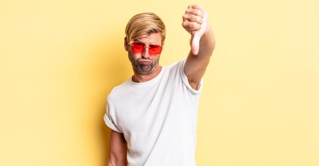 Homem adulto loiro se sentindo zangado, mostrando os polegares para baixo e usando óculos escuros