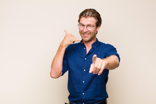 Homem adulto loiro sorrindo alegremente e apontando para a frente enquanto faz um gesto para ligar para você, falando ao telefone