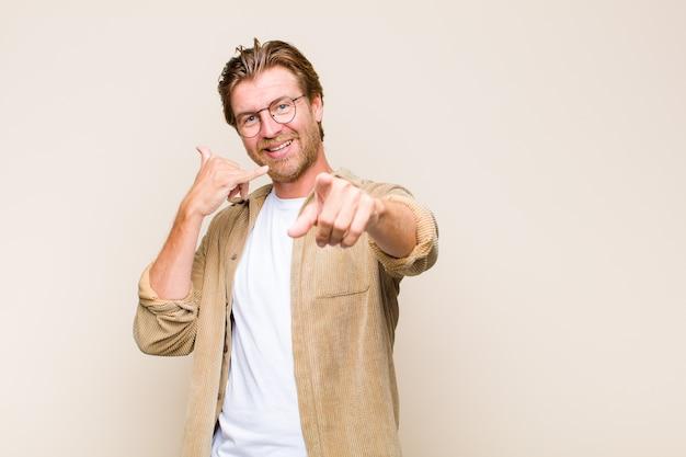 Homem adulto loiro sorrindo alegremente e apontando para a frente enquanto faz um gesto para ligar para você, falando ao telefone Foto Premium