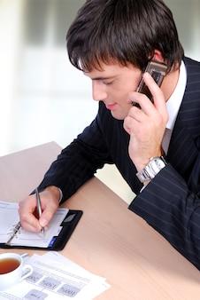 Homem adulto médio falando ao telefone e escrevendo no organizador.