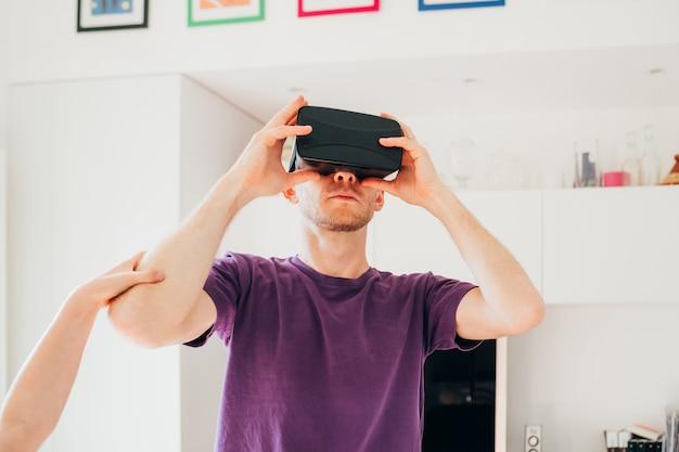 Homem adulto médio interior em casa usando o visualizador em 3d