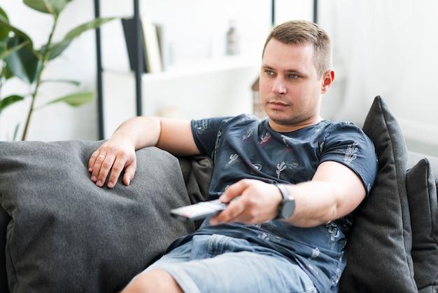Homem adulto meio, sentando, ligado, sofá, olhando tv