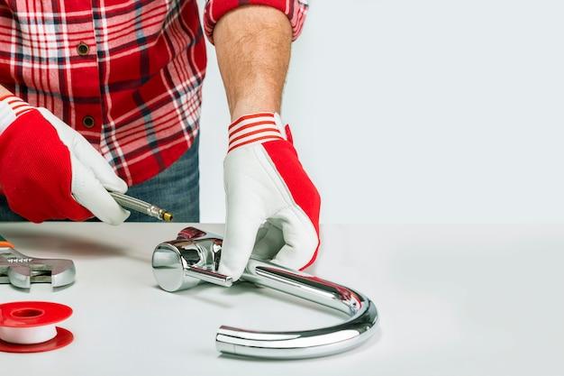Homem adulto montando ou consertando torneira de pia de cozinha
