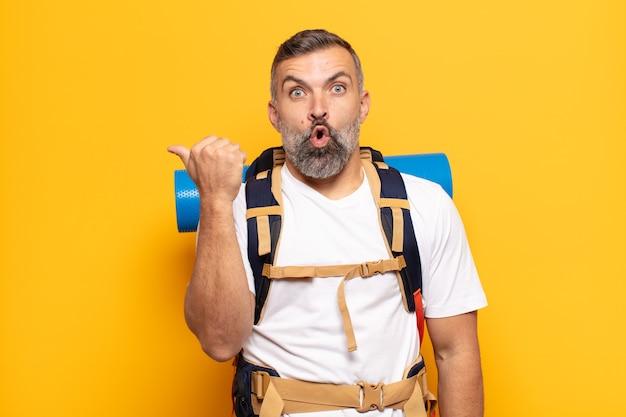 Homem adulto parecendo surpreso em descrença, apontando para um objeto ao lado e dizendo uau, inacreditável