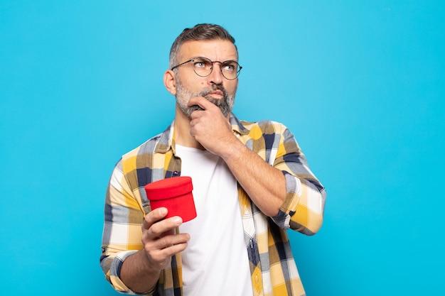 Homem adulto pensando, sentindo-se duvidoso e confuso, com diferentes opções, imaginando qual decisão tomar