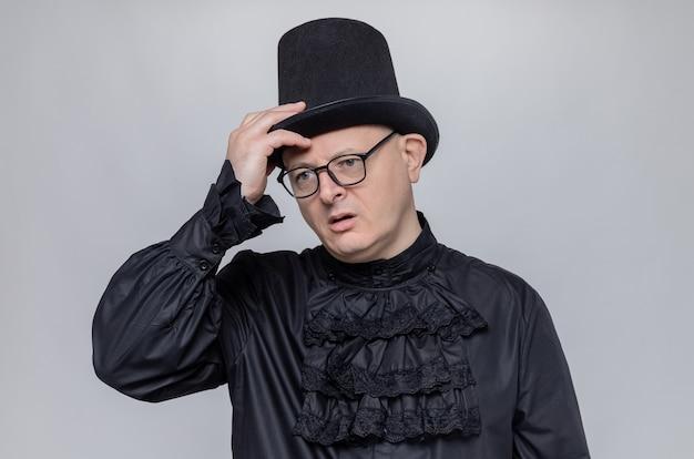 Homem adulto pensativo com cartola e óculos na camisa gótica preta, colocando a mão no chapéu e olhando para o lado