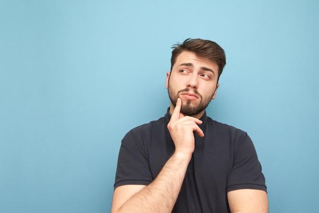 Homem adulto pensativo está isolado no azul