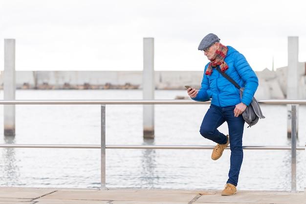 Homem adulto pensativo, vestindo jaqueta azul e usando o smartphone