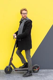 Homem adulto posando com sua scooter elétrica