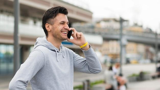 Homem adulto positivo falando ao telefone