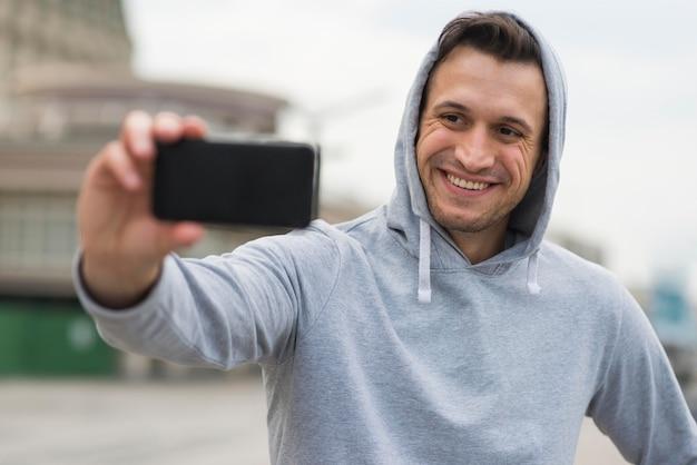 Homem adulto positivo tomando uma selfie