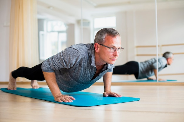 Homem adulto praticando posições de ioga