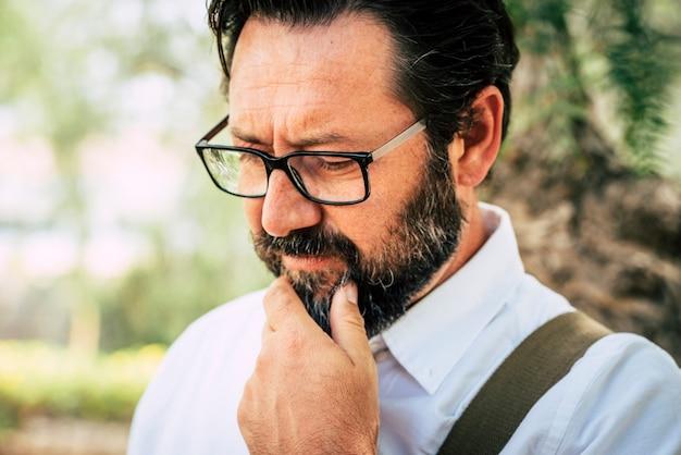Homem adulto preocupado, caucasiano, de 50 anos, toca a barba e pensa sozinho - óculos e pessoas ao ar livre com o fundo desfocado do parque verde