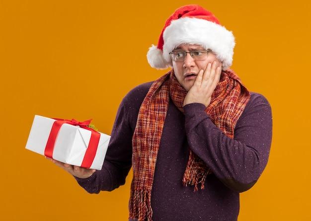 Homem adulto preocupado usando óculos e chapéu de papai noel com lenço no pescoço segurando e olhando para o pacote de presente, mantendo a mão no rosto isolado na parede laranja
