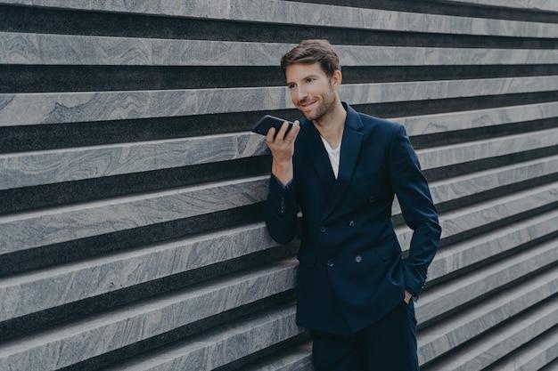 Homem adulto próspero profissional com barba por fazer usa alto-falante e atende a chamada