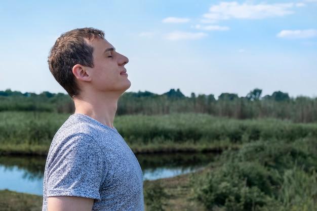 Homem adulto relaxado respirando ar fresco ao ar livre com o lago e o campo ao fundo