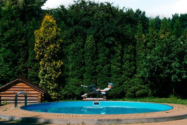 Homem adulto relaxante na espreguiçadeira além da piscina