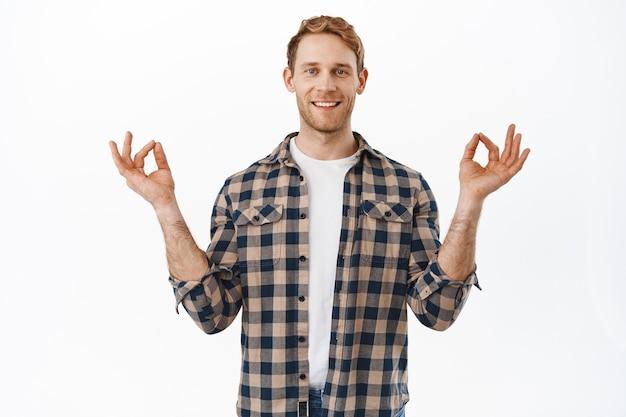 Homem adulto ruivo sorridente, paciente e relaxado, meditando, sentindo-se em paz, respirando e descansando em ioga, segurando as mãos em pose de lótus nirvana, parede branca