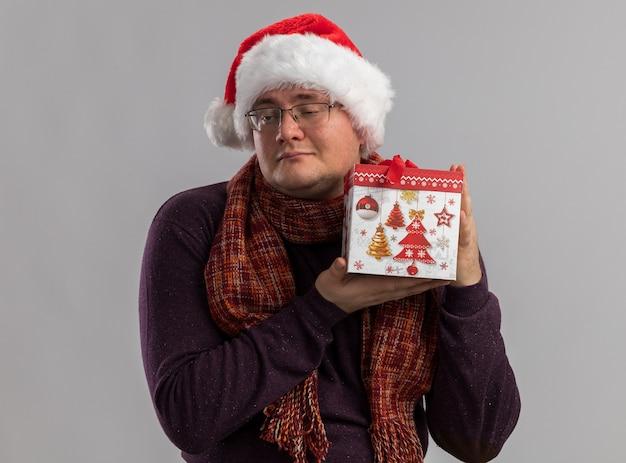 Homem adulto satisfeito usando óculos e chapéu de papai noel com lenço no pescoço segurando um pacote de presente de natal, olhando para o lado isolado na parede branca
