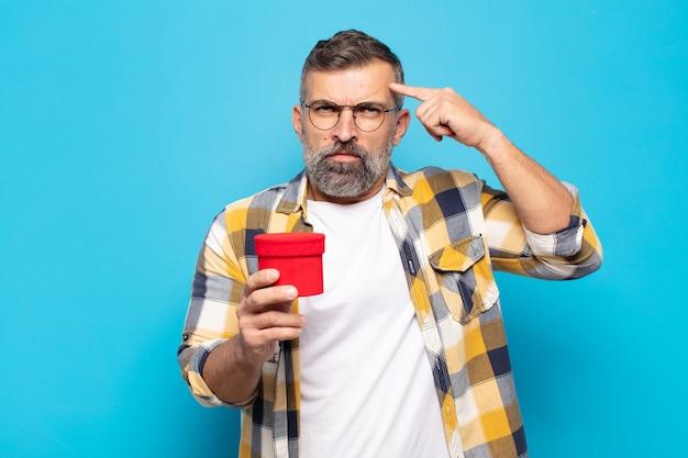 Homem adulto se sentindo confuso e perplexo, mostrando que você é louco, louco ou maluco