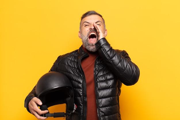 Homem adulto se sentindo feliz, animado e positivo, dando um grande grito com as mãos perto da boca, gritando
