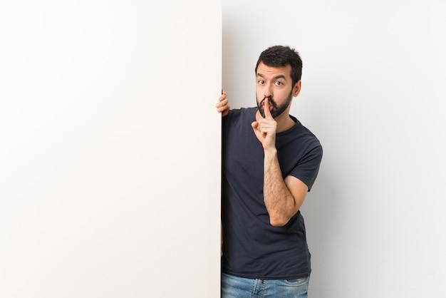 Homem adulto, segurando um grande cartaz vazio e fazendo gesto de silêncio