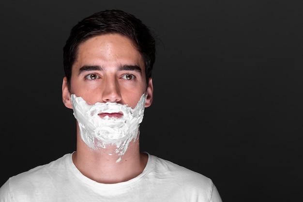 Homem adulto sério com creme de barbear