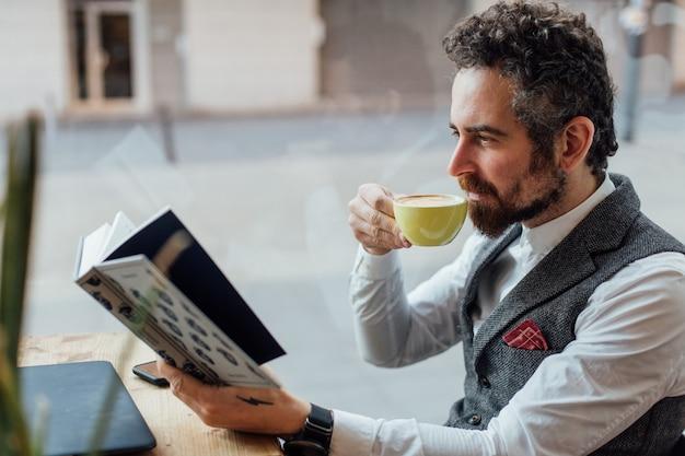 Homem adulto sério de meia-idade bebe e aprecia uma bebida de café enquanto lê um livro interessante e cativante em um café ou biblioteca