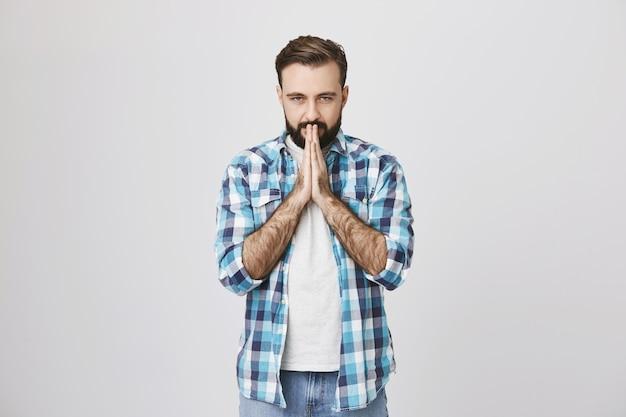 Homem adulto sério e preocupado implorando, orando