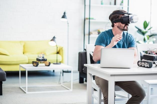 Homem adulto sério sentado à mesa enquanto testifica os óculos de realidade virtual em casa