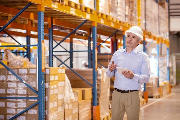 Homem adulto sério usando capacete enquanto verifica o equipamento no depósito