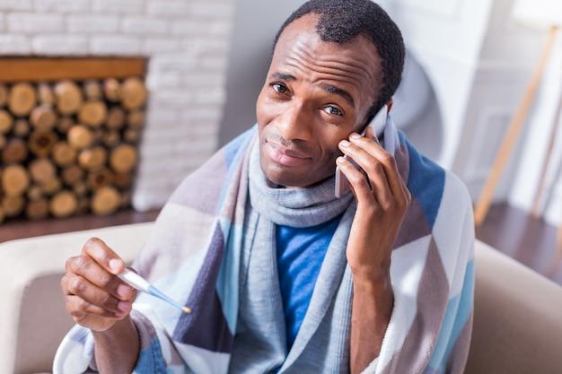 Homem adulto simpático e simpático segurando um termômetro e olhando para você enquanto fala ao telefone