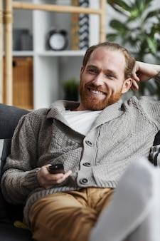 Homem adulto sorridente assistindo tv