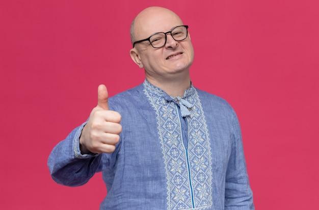 Homem adulto sorridente com camisa azul e óculos apontando para cima