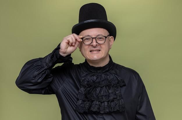 Homem adulto sorridente com cartola e óculos em uma camisa gótica preta