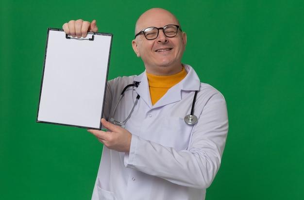 Homem adulto sorridente com óculos em uniforme de médico com estetoscópio segurando a prancheta e olhando