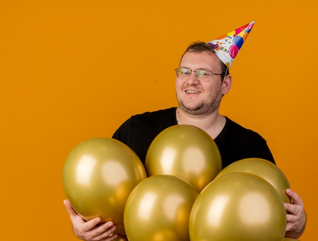 Homem adulto sorridente com óculos óticos e boné de aniversário com balões de hélio isolados na parede laranja