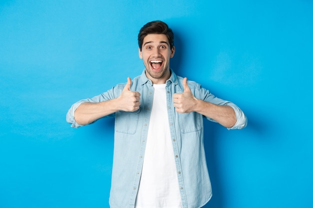 Homem adulto sorridente mostrando os polegares para cima com uma cara animada, como algo incrível, aprovando o produto, de pé contra a parede azul