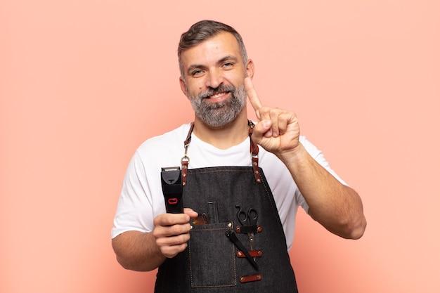 Homem adulto sorrindo e parecendo amigável, mostrando o número um ou primeiro com a mão para a frente, em contagem regressiva