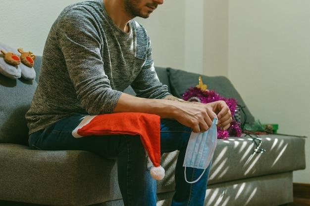 Homem adulto sozinho em casa no natal de 2020 com chapéu e máscara de natal. conceito de solidão e tristeza. confinado