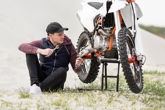 Homem adulto tentando reparar moto
