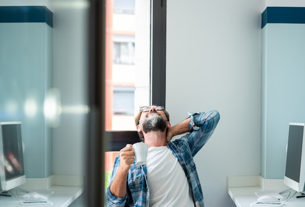 Homem adulto tocando seu pescoço e costas devido ao estresse, dor e doenças causadas pela postura de trabalho - homem adulto maduro sofre de problema nas costas sentado no assento no escritório de trabalho - estilo de vida de pessoas cansadas freelance