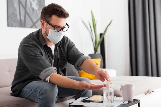 Homem adulto usando desinfetante para as mãos em casa