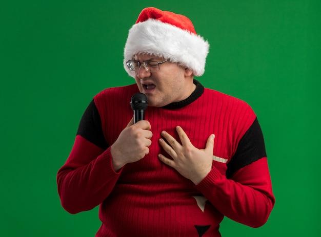 Homem adulto usando óculos e chapéu de papai noel segurando o microfone cantando com os olhos fechados, mantendo a mão no peito isolado sobre fundo verde