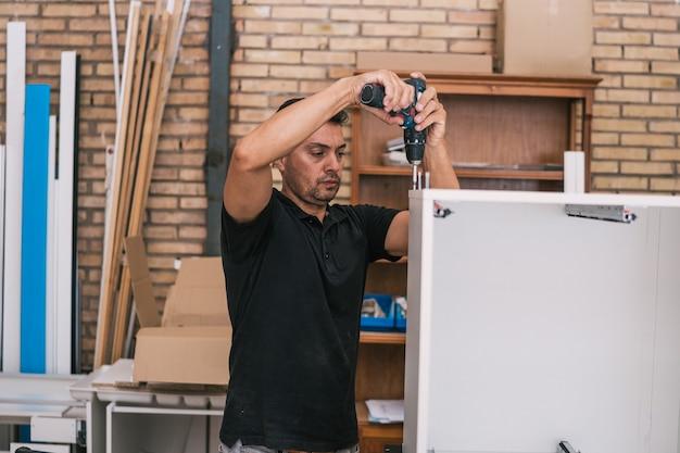 Homem adulto usando uma furadeira para consertar duas peças de uma estrutura de madeira em uma oficina