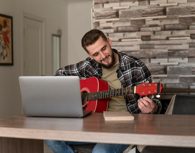 Homem afinando guitarra, tiro médio