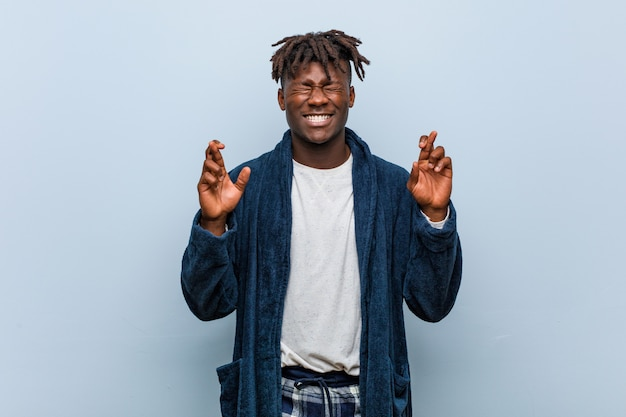 Homem africano africano novo que veste os dedos do cruzamento do pijama para ter a sorte