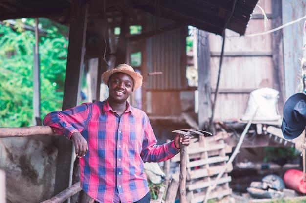 Homem africano agricultor está de pé no seu local de trabalho perto de vacas na fazenda